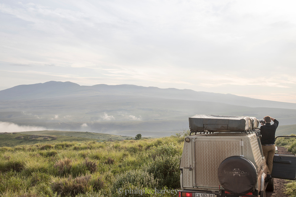 Rear view of a male adult tourist taking a picture from a safari car in the Ngorongoro Highlands, Tanzania