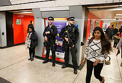 © Licensed to London News Pictures. 27/04/2017. London, UK. Extra armed police officers watch over commuters at Green Park Tube station in London, shortly after a man was arrested carrying a bag full of knives, on Whitehall in Westminster, central London. Photo credit: Tolga Akmen/LNP