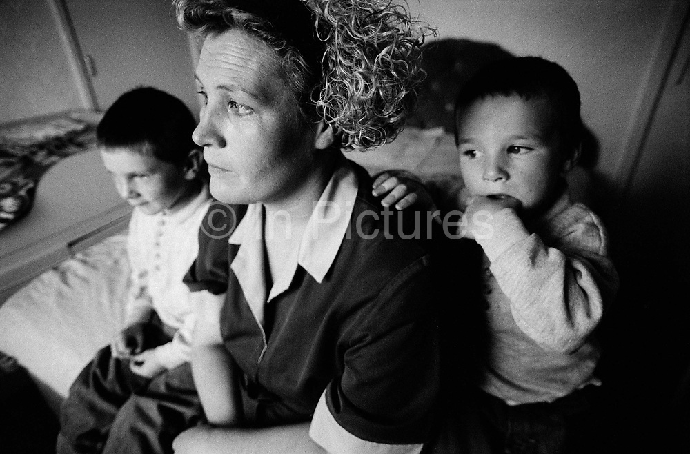A mother and her two children in their cramped, cold bedroom where they all sleep on the Northwood Estate in Kirkby, Merseyside, a notoriously run down inner city area