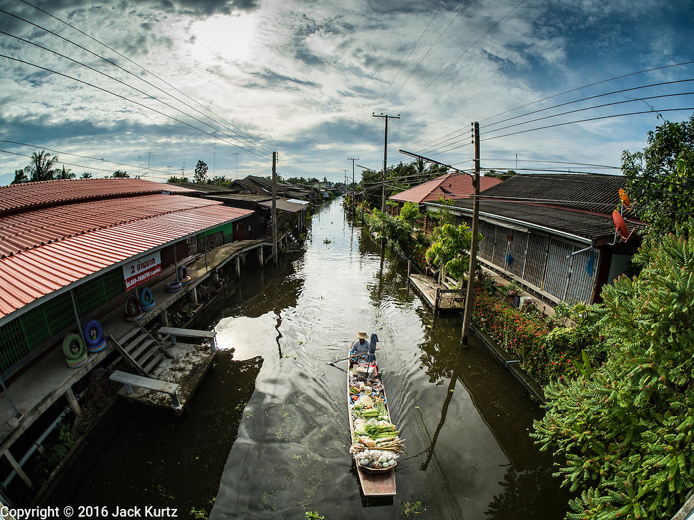 27 SEPTEMBER 2016 - BANGKOK, THAILAND:  A vendor paddles her canoe of produce through the floating market in Damnoen Saduak, Thailand. The market is famous because vendors cruise the canals around the market selling produce and tourist curios. It is one of the best known tourist attractions in Samut Songkhram province.     PHOTO BY JACK KURTZ