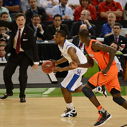 Mar 31, 2012; New Orleans, LA, USA; Kentucky Wildcats guard Darius Miller (center) dribbles as Louisville Cardinals center Gorgui Dieng (right) defends and head coach Rick Pitino (left) reacts during the second half in the semifinals of the 2012 NCAA men's basketball Final Four at the Mercedes-Benz Superdome. Mandatory Credit: Derick E. Hingle-US PRESSWIRE