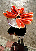 Portrait of a woman selling watermelon slices from the top of her head in Leon, Nicaragua.