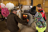 Alison Nutter, Brent Howard and Jacoby Drouin get a first look at the fire box of the evaporator with Michael Bolduc in their new sap house at Gilford Elementary School.  (Karen Bobotas/for the Laconia Daily Sun)