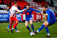 Luther Wildin of Stevenage goes in to tackle Josh McPake of Harrogate Town during the EFL Sky Bet League 2 match between Stevenage and Harrogate Town at the Lamex Stadium, Stevenage, England on 6 March 2021.