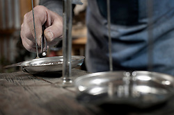 Senior male goldsmith checking silvers on scale at workshop, Bavaria, Germany