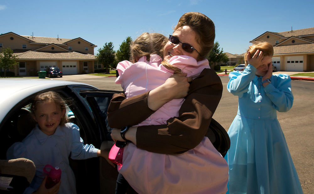 FLDS mother Sarah Barlow Draper holds her daughter Autumn (cq) outside their home in Abilene, Texas on Monday June 2, 2008.  At left is her daughter Danielle and at right is her other daughter Rebekah (cq). They had reunited with their mother following the court order which released the children back into the custody of their mothers. August MIller/ Deseret News .