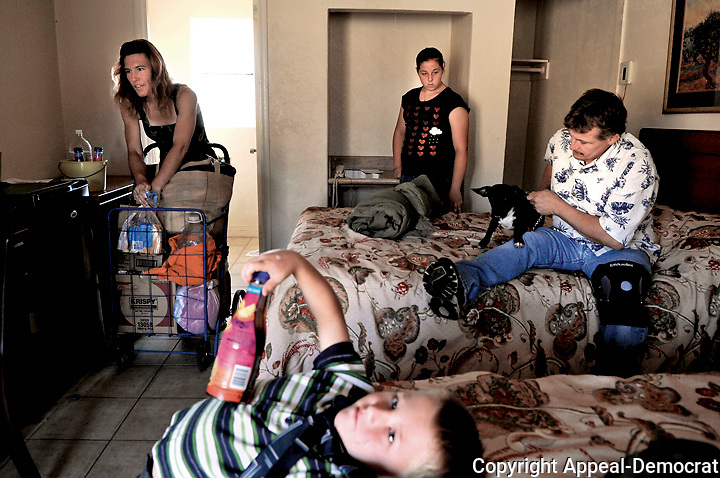 From left, Katrina Wallis,35, Jerald Thomas Wallis,6, Savannah Wallis,15, and Jerald Kenneth Wallis Jr.,41, holding the family dog Buddy, pack their belongings before checking out of the Rio Inn and Suites on North Beale Road Saturday June 26  in Linda. The Wallis family with the help of references from several charity groups was able to find a suitable apartment and as of Friday July 2 are no longer homeless.
