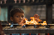 A boy purifies himself with the smoke from holy candles at Swayambunath Stupa in Kathmandu.