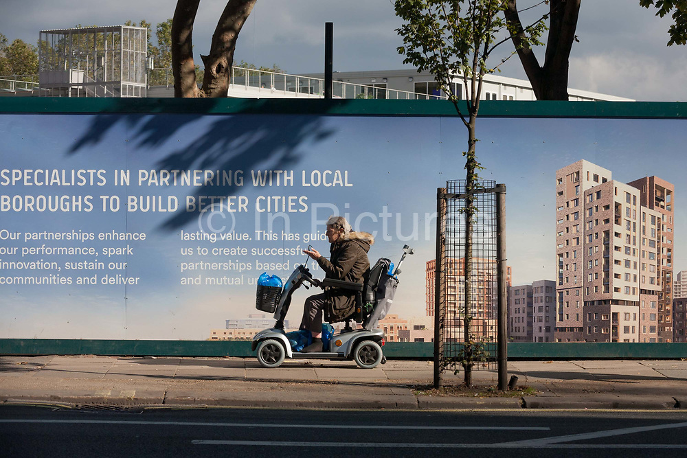 A disabled in a mobility scooter lady passes a regeneration project hoarding at Elephant Park, Elephant & Castle, on 11th October 2016, in London, England. Southwark Council's development partner, Lendlease is regenerating over 28 acres across three sites at the heart of Elephant & Castle, in what is the latest major regeneration opportunity in zone 1 London. The vision for the £1.5 billion regeneration is to build on the area's strengths and vibrant character in order to re-establish Elephant & Castle as one of London's most flourishing urban quarters. The Elephant & Castle regeneration is of a scale rarely seen in central London and includes almost 3,000 new homes, plus office, retail, community, leisure and restaurant space.