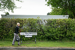 © Licensed to London News Pictures. 07/05/2015. Tamworth, Staffordshire, UK. Polling stations opened at 7 am on the day of the General Election. Pictured, an early voter makes her way to the Polling Station, pictured behind the hedge, in Buckingham Road, Tamworth. Photo credit : Dave Warren/LNP