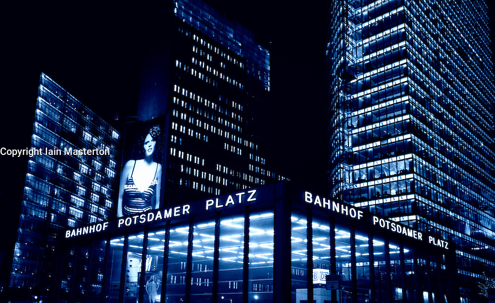 Night view of high rise buildings and railway station entrance at Potsdamer Platz in Mitte Berlin Germany