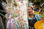 16 MARCH 2013 - ALONG HIGHWAY 13, LAOS:  A woman carries a tree of money to make merit at the temple fair at Wat Nong Sa in the village of Nong Sa, which is on Highway 13, in Vientiane province of Laos. The paving of Highway 13 from Vientiane to near the Chinese border has changed the way of life in rural Laos. Villagers near Luang Prabang used to have to take unreliable boats that took three hours round trip to get from the homes to the tourist center of Luang Prabang, now they take a 40 minute round trip bus ride. North of Luang Prabang, paving the highway has been an opportunity for China to use Laos as a transshipping point. Chinese merchandise now goes through Laos to Thailand where it's put on Thai trains and taken to the deep water port east of Bangkok. The Chinese have also expanded their economic empire into Laos. Chinese hotels and businesses are common in northern Laos and in some cities, like Oudomxay, are now up to 40% percent. As the roads are paved, more people move away from their traditional homes in the mountains of Laos and crowd the side of the road living off tourists' and truck drivers.   PHOTO BY JACK KURTZ