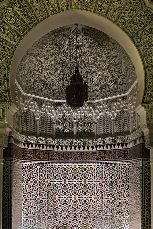Mihrab, niche facing mecca, with zellige tiles and carved stucco, in the prayer hall, Grande Mosquee de Paris, designed by Robert Fournez, Maurice Mantout and Charles Heubes, built in Neo-Mudejar style 1922-26 and inaugurated in 1926, as a gesture of thanks to the muslim soldiers who fought in France's colonial troops during the First World War, in the 5th arrondissement of Paris, France. The mosque is built from reinforced concrete, with wooden carvings and mosaics brought from Morocco. The religious spaces include the grand patio, prayer room and minaret, there is an Islamic school and library, and a cafe and hammam or Turkish baths. The mosque was renovated in 1992. Picture by Manuel Cohen