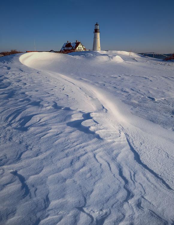 Curve of wind-blown snow drift, leading line to Portland Head Light, in winter, Cape Elizabeth, ME