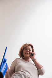Happy senior woman talking on mobile phone and holding a watering can, Munich, Bavaria, Germany