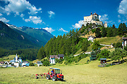 Farmer turning hay at Tarasp in the Lower Engadine Valley, Switzerland