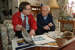 Housing Officer and tenant look at brochures to choose a new kitchen in a housing association flat,