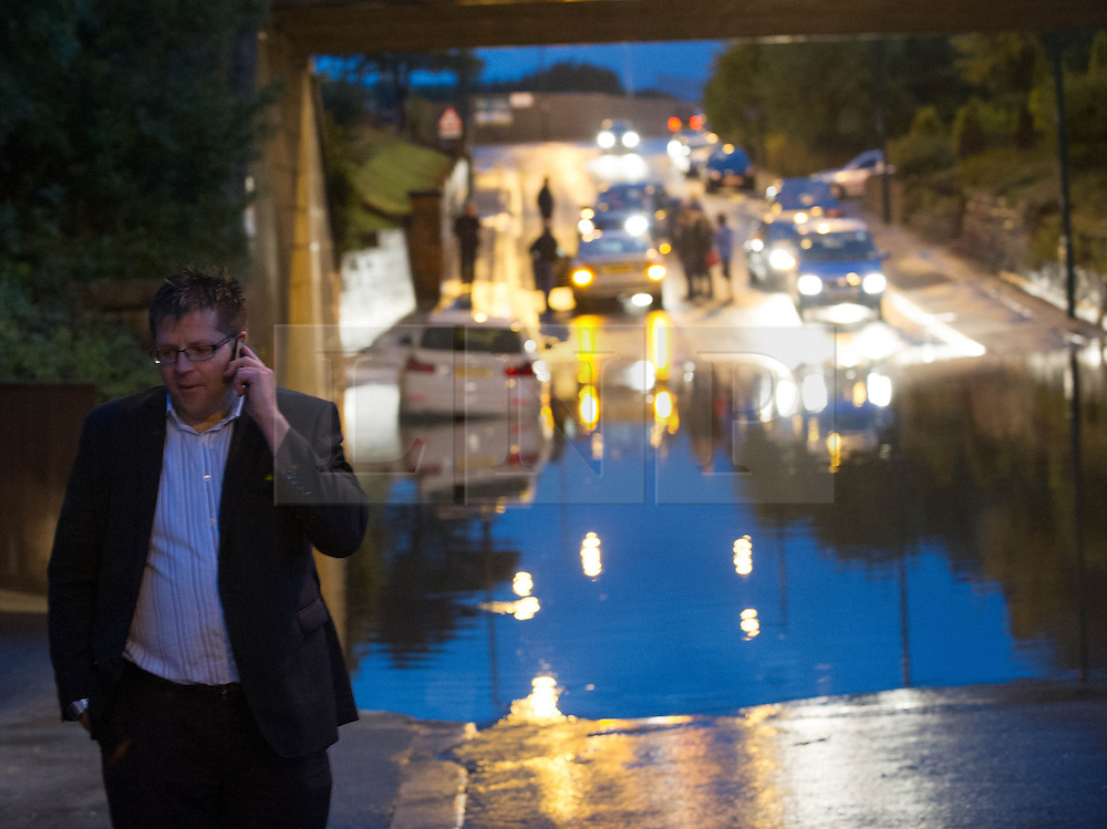 © Licensed to London News Pictures. 06/09/2013<br /> <br /> Saltburn, Cleveland, England<br /> <br /> A man talks on his phone as heavy flooding hits in Saltburn in Cleveland causing the A174 road to be blocked due to the floods.<br /> <br /> Photo credit : Ian Forsyth/LNP