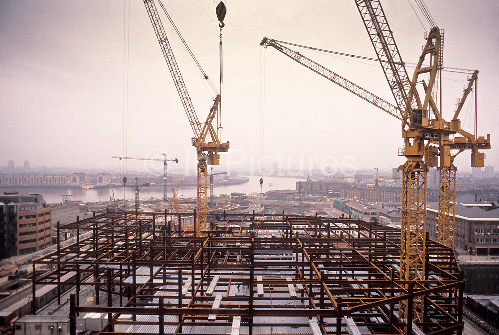 After the old Canary Wharf was demolished, cranes can be seen across the Docklands in its process of redevelopment, seen in the foreground the building of the basic structure which would become Canada Square, London, UK