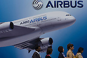 Delegates walk past a billboard of an A380 airliner outside one of the EADS company's chalets at the Farnborough Air Show.