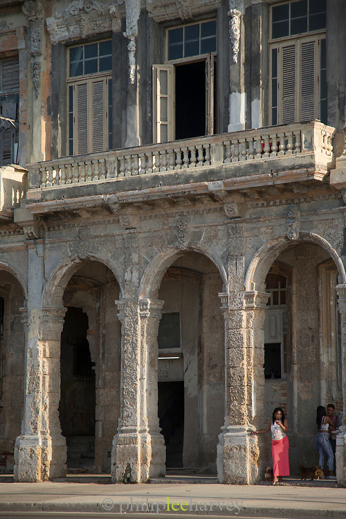 People on city street - buildings with architecture arches, Malecon road, Havana, Cuba