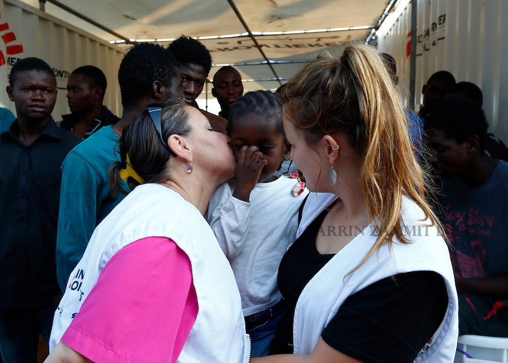 A Medecins san Frontiere (MSF) nurse kisses a Congolese child on the MSF rescue ship Bourbon Argos as it arrives in Trapani, on the island of Sicily, Italy, August 9, 2015.  Some 241 mostly West African migrants on the ship arrived on the Italian island of Sicily on Sunday morning, according to MSF.<br /> REUTERS/Darrin Zammit Lupi <br /> MALTA OUT. NO COMMERCIAL OR EDITORIAL SALES IN MALTA