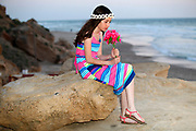 Preteen in colourful dress holds a flower bouquet while siting and waiting on the beach for the return of her long lost lover (or father)