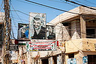 Tyre, Lebanon - September 1, 2010: Faded posters of Yasser Arafat are on display in the Al-Bass Palestinian Refugee Camp, obscured by a tangle of utility wires in this densely crowded neighborhood