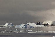 Moody clouds over icebergs at the northern end of Peter 1 Øy, Phantom Coast, Antarctica