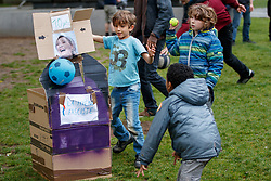 © Licensed to London News Pictures. 07/05/2017. Paris, France. French children attack a cardboard with Marine Le Pen's pictures attached on it as people protest and boycott against the second round of the presidential election in La Villette park in Paris on Sunday, 7 May 2017. Photo credit: Tolga Akmen/LNP