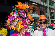 New York, NY, USA-27 March 2016. A couple dressed for the day, the woman wearing a tall, wide and elaborate floral hat  in the annual Easter Bonnet Parade and Festival.