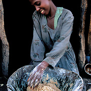 Asmara uses the time she has gained from having the well nearby for preparing the injera, unleavened bread made with indigenous cereal, for lunch. Raya-Mehoni, Ethiopia.
