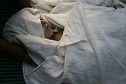 Women put the linen shroud over the dead body of Qamar, center, a 26-year-old tuberculosis patient who died of postpartum complications two weeks after the delivery, before the burial, Shohada district in Badakshan province, Afghanistan, Monday, May 21, 2007.