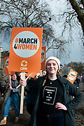 March 4th 2017. Thousands of people, mostly women and girls, marched across Tower Bridge in an event organised by Care International to mark International Womens Day March 8th and the need for gender equality. A young woman holds a placard saying March for women and wears a t-shirt which says Feminist with a to do list.