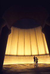 Stock photo of a man and woman standing inside the waterwall fountain in Houston Texas