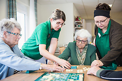 Senior inhabitants playing board game with nurse in rest home
