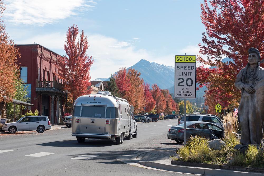 Truck towing an Airstream trailer through downtown Joseph, Oregon on an autumn day.