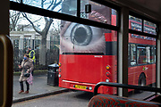 A pedestrian passes a large eye on the rear of a London bus, which urges motorists to reduce their speeds on the capitals roads, on 11th March 2021, in London, England.