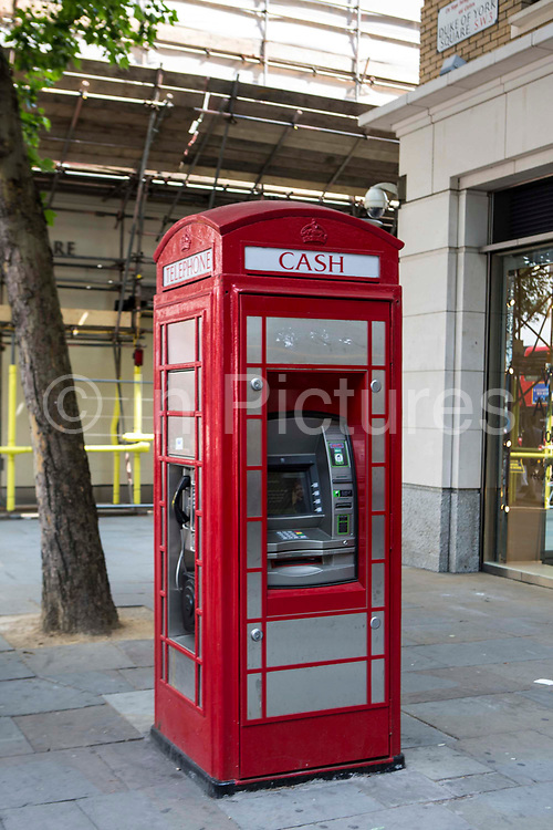 A traditional British red phone box which has been modernized and customised into include a banking ATM cash machine on one side on Duke of York Square, London, United Kingdom.