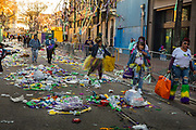 Walking through the beads and trash thrown from floats on the Endymion parade during Mardi Gras on 23rd February 2020 in New Orleans, Louisiana, United States. Mardi Gras is the biggest celebration the city of New Orleans hosts every year. The magnificent, costumed, beaded and feathered party is laced with tradition and  having a good time. Celebrations are concentrated for about two weeks before and culminate on Fat Tuesday the day before Ash Wednesday and Lent. The average Endymion rider will throw 500 pounds of beads and officials estimate overall upwards of 25 million pounds of Mardi Gras items get tossed from floats, more than half of which winds up on New Orleans streets.