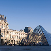 Facade and glass pyramid of Louvre museum, Paris.