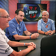 NCAA basketball coaches Jim Boeheim, Mike Krzyzewski and Roy Williams share a light moment while on air at ESPN's studio in Charlotte, N.C. during ACC Media Day.  ©Travis Bell Photography