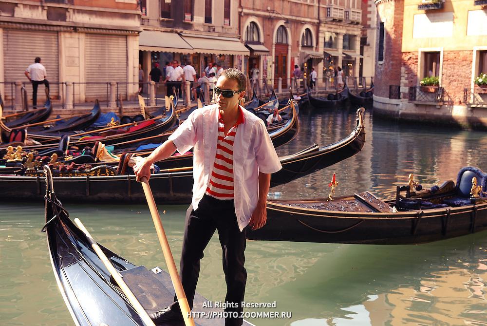 Gondolier on his gondola closeup in Venice canal