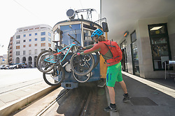 Young biker loading bikes on cable car