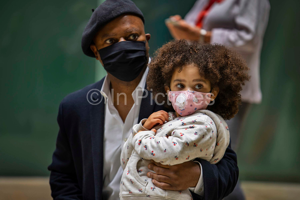 Ben Okri with his daughter Mirabella, 'Can't you hear the future weeping? Our love must save the world' is a statement by the writer Ben Okri which was revealed in a live art piece by eco Artists Ackroyd & Harvey on 25th July 2021 in the Turbine Hall of Tate Modern, London, United Kingdom. Conceived as a message to us all, the artists were calling yet again for us to act in the face of our climate crisis. In the temporary 'greenhouse' of Tate, the seeds burst into life with the added dimension of Okri's clarion call to use active love to inspire the change we need. Stencilled letters, blocking the light, then removed, created the message within the grass. For the final act, in a solemn ritual, the grass banner was rolled up, carried out by volunteer performers and floated on the Thames. Visible from up high, floating on the tidal river, the luminescent yellow letters stood out boldly from the rich green of the grass. At the end of the day the banner was dismantled and the grass art distributed to anyone who wanted to continue to grow the words.