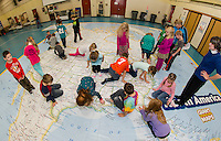 Belmont Elementary second graders search for their assigned state on the interactive map with Phys Ed Teacher Mrs. Nims and Principal Sheila Arnold.  Each class will spend a class period during the two days the North America interactive map is in Belmont.  (Karen Bobotas/for the Laconia Daily Sun)