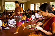 """Students and teachers have lunch and rest after an intense morning's  session of dance practice and routines  at the traditional and highly prestigious Kalakshetra school for the arts, Chennai. The school was founded in 1936 and due to its exacting and demanding schedule is considered India's formost classical dance academy of this ancient cultural art heritage that is informally known as """"temple dancing"""" and that dates back to the Natya Shastra, the 2000 year old text that lays down the principles of Indian dramatic theory and performance. Tamil Nadu, India."""