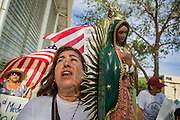"19 JULY 2012 - PHOENIX, AZ:  ROSA MARIA SOTO carries a statue of the Virgin of Guadalupe and prays during a march around the US Courthouse in Phoenix on the first day of a class action lawsuit, Melendres v. Arpaio in Phoenix Thursday. The suit, brought by the ACLU and MALDEF in federal court against Maricopa County Sheriff Joe Arpaio, alleges a wide spread pattern of racial profiling during Arpaio's ""crime suppression sweeps"" that targeted undocumented immigrants. U.S. District Judge Murray Snow granted the case class action status opening it up to all Latinos stopped by Maricopa County Sheriff's Office deputies during the crime sweeps. The case is being heard in Judge Snow's court.  PHOTO BY JACK KURTZ"