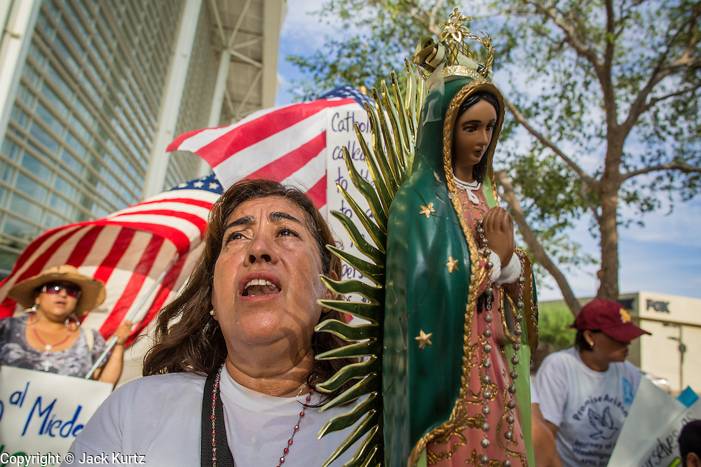 """19 JULY 2012 - PHOENIX, AZ:  ROSA MARIA SOTO carries a statue of the Virgin of Guadalupe and prays during a march around the US Courthouse in Phoenix on the first day of a class action lawsuit, Melendres v. Arpaio in Phoenix Thursday. The suit, brought by the ACLU and MALDEF in federal court against Maricopa County Sheriff Joe Arpaio, alleges a wide spread pattern of racial profiling during Arpaio's """"crime suppression sweeps"""" that targeted undocumented immigrants. U.S. District Judge Murray Snow granted the case class action status opening it up to all Latinos stopped by Maricopa County Sheriff's Office deputies during the crime sweeps. The case is being heard in Judge Snow's court.  PHOTO BY JACK KURTZ"""