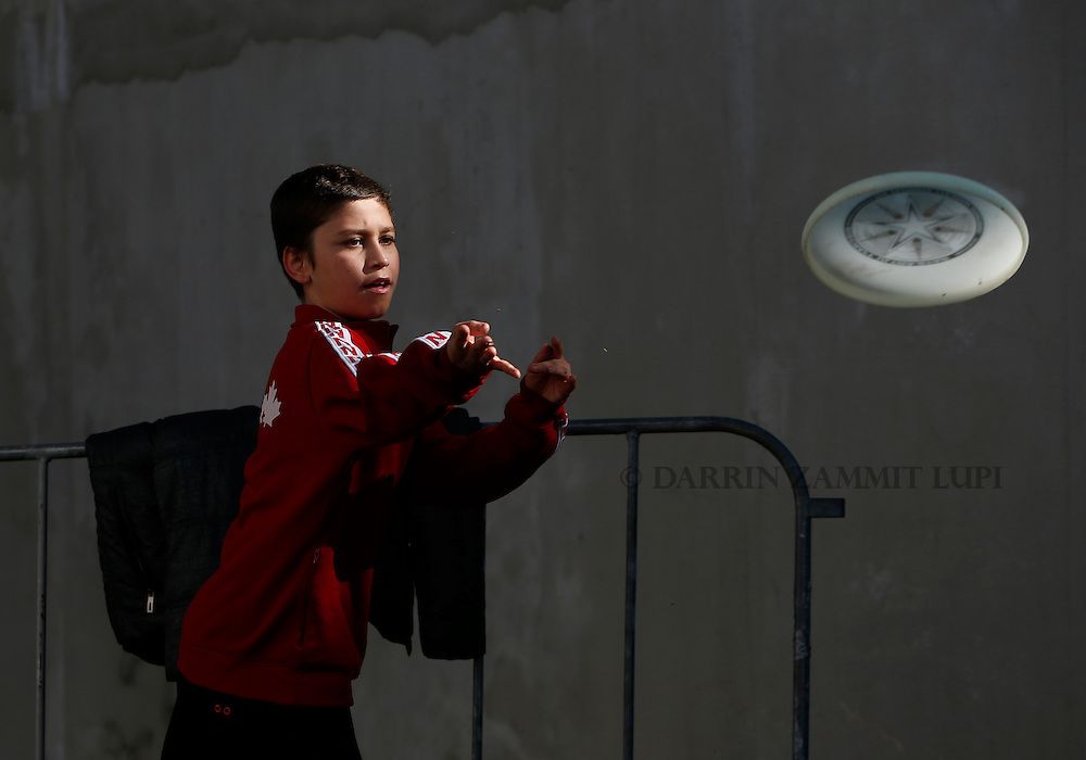 A boy throws a frisbee as migrants and refugees wait to continue their train journey to western Europe at a refugee transit camp in Sid, Serbia, February 11, 2016.<br /> Photo: Darrin Zammit Lupi